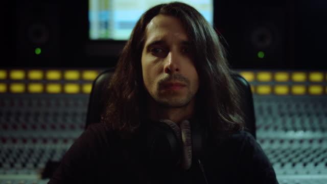 kompozytor włącza krzesło w studio. inżynier dźwięku słuchający muzyki w pomieszczeniu. - długie włosy filmów i materiałów b-roll