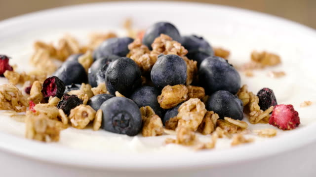 vídeos de stock e filmes b-roll de composition of a typical genuine breakfast made with yogurt, blueberries, raspberries, blackberries, muesli. - oats