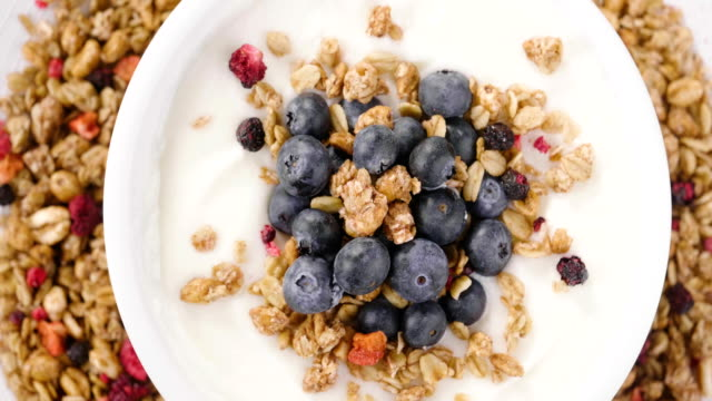 vídeos de stock e filmes b-roll de composition of a typical genuine breakfast made with yogurt, blueberries, raspberries, blackberries, muesli. - granola
