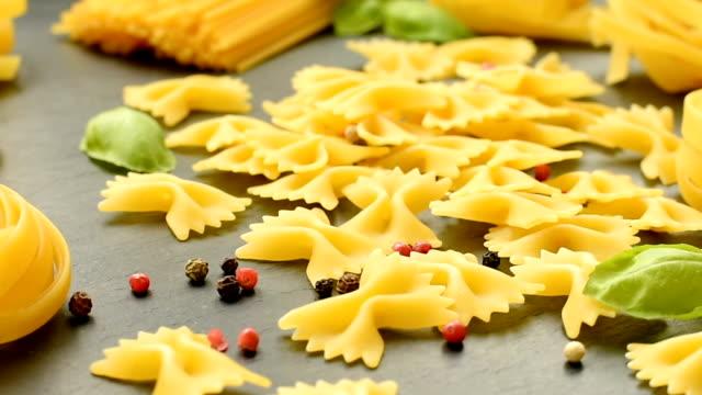 zusammensetzung der trockene teigwaren, schwarzer pfeffer, basilikum und tomaten - glutenfrei stock-videos und b-roll-filmmaterial