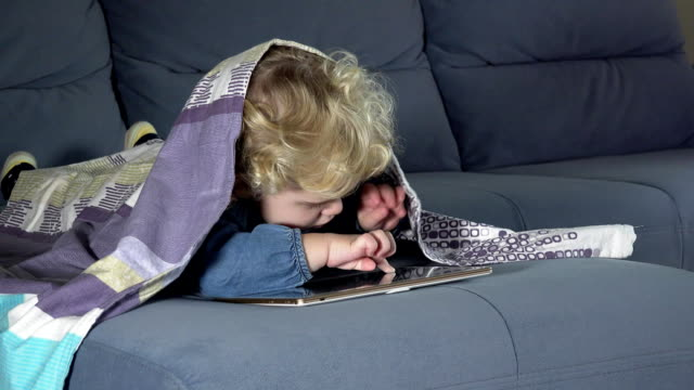 Computer addict child touching tablet computer screen. Girl covered with plaid video