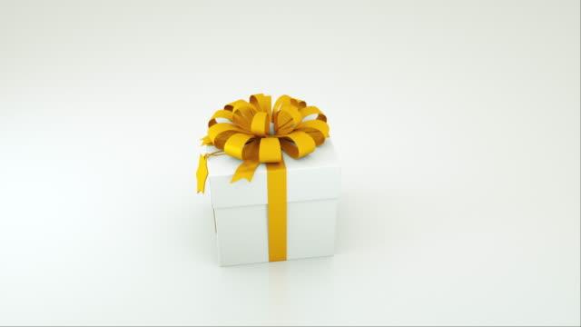 白い背景に隔離された金色の弓とタグを持つ白いギフトボックスのコンピュータ生成画像。3d レンダリング - プレセントの箱点の映像素材/bロール