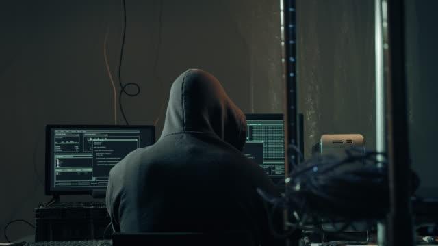 компьютерный хакер набрав код на сетевых компьютерах кража данных - шифрование стоковые видео и кадры b-roll