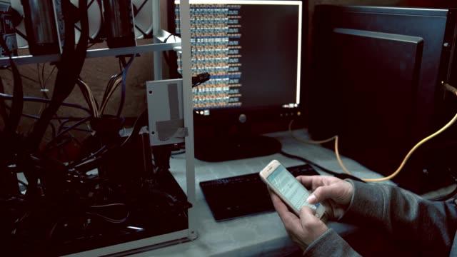 haker komputerowy z inteligentnym językiem programowania telefonu w komputerze, w czasie rzeczywistym - spyware filmów i materiałów b-roll