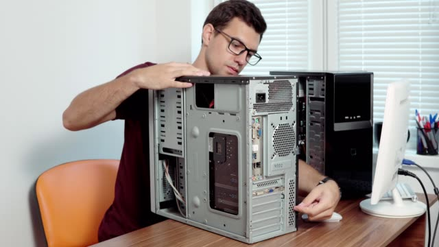Computer service worker repair a broken computer in the office using a screwdriver and upgrading computer hardware. Support team. Computer maintenance. Shot in 4k video