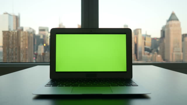 Computer with Greenscreen in Modern Office Building with Cityscape Background.