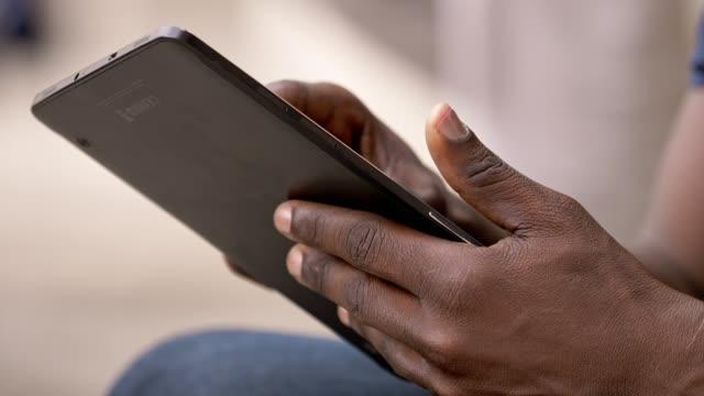 comunication, modernity, life- black man's hands using digital tablet- outdoor video