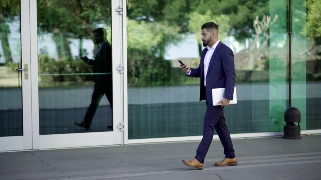 路上でスマートフォンを使用した集中ビジネスマン - 全身点の映像素材/bロール