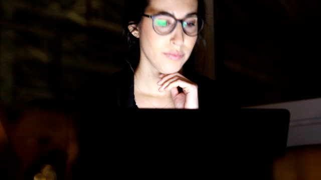 Concentrated businesswoman using laptop in office video