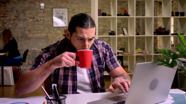 긴 검은 머리와 수염과 집중 된 백인 남성은 노트북에 입력 하 고 그의 직장에서 놀고 있는 동안 빨간 컵에서 마시는, 현대 사무실 그림 - 한 명의 중년 남자만 스톡 비디오 및 b-롤 화면