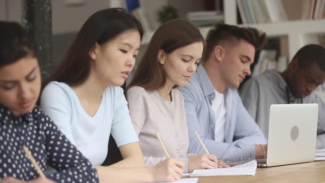 konzentrierte kaukasische student unter internationalen klassenkameraden schreiben notizen hören vortrag - zuschauerraum stock-videos und b-roll-filmmaterial