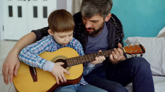 concentrated child is playing guitar with his father experienced guitarist, adjusting musical instrument and enjoying happy moments. music and family concept. - гитара стоковые видео и кадры b-roll