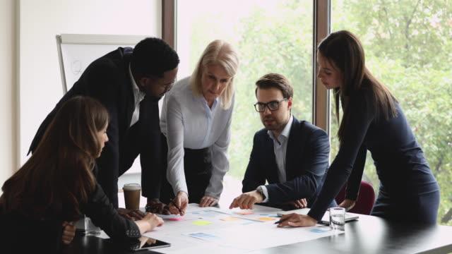 vídeos de stock e filmes b-roll de concentrated different ages diverse business people analyzing marketing paper reports. - envolvimento dos funcionários