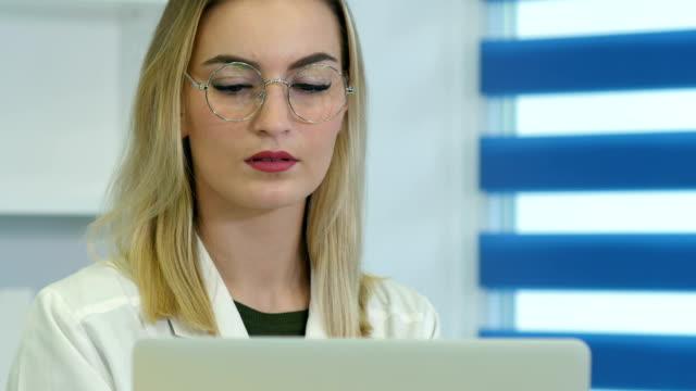 Vrouwelijke arts geconcentreerd in glazen werken op laptop bij receptie video