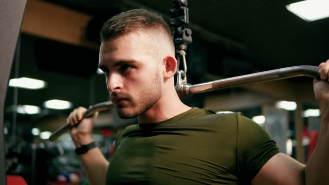 Concentrated handsome man exercising his chest muscles and training his shoulders in the gym. Shot in 4k video