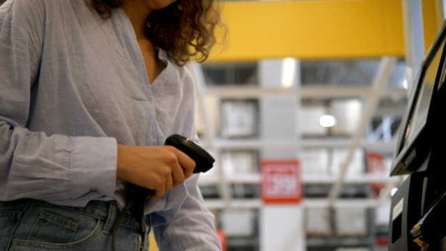 concentrated lady holds barcode scanner and scans goods - vídeo