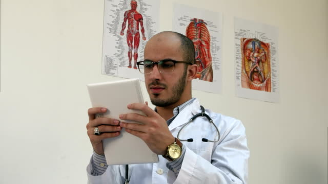 Concentrated male medical worker using digital tablet video