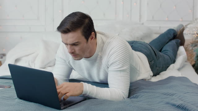 Concentrated man laying with computer on bed in luxury house. Concentrated man laying with computer on bed in luxury house. Handsome business man typing laptop in remote workplace. Focused guy looking pc screen in christmas decorated room. double bed stock videos & royalty-free footage
