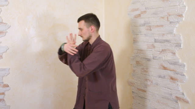 Concentrated man practicing tai chi martial gymnastics on wooden wall background. Fit young man training traditional qigong breathing and movement exercises.