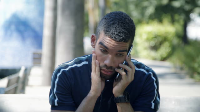 Concentrated man talking on phone outside, looking shocked