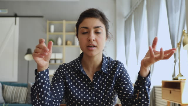 Concentrated millennial female professional tutor giving online class. Head shot focused young indian woman sitting at desk, looking at camera, communicating via video call with client. Concentrated millennial female professional tutor recording giving online class. conference call stock videos & royalty-free footage