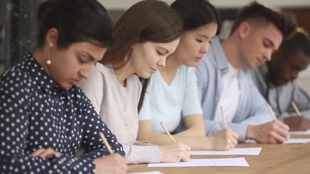 studenti di razza mista concentrati seduti a tavola alla lezione didattica. - rispondere video stock e b–roll