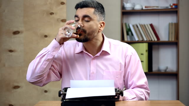 Concentrated old-school author typing book on vintage typewriter in his office video