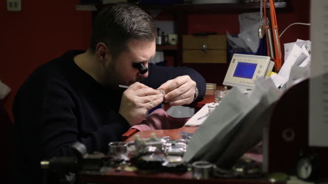 Concentrated watchmaker repairing vintage pocket watch at workshop