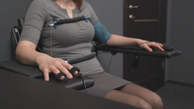 Concentrated woman answering questions with pulse sensors Close up of young lady in grey dress sitting in black chair with pulse indicators on fingers and body. Female worried about test results from lie detector procedure electrode stock videos & royalty-free footage