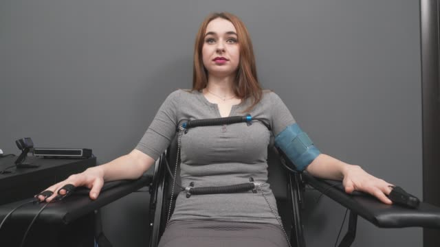 Concentrated woman answering questions with pulse sensors Front view of concentrated woman with long hair connected to indicators measuring pulse during lie detector test. Sincere young girl in grey dress sitting in chair and answering questions. electrode stock videos & royalty-free footage