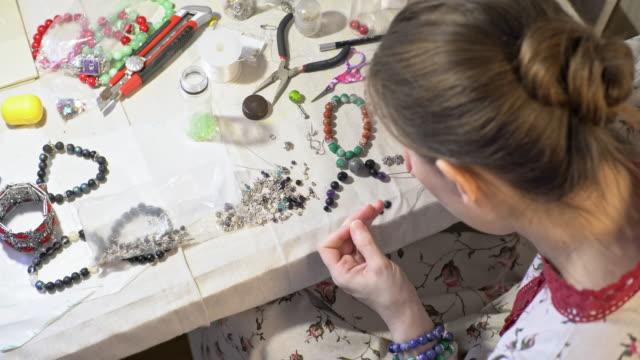 концентрированная женщина изготовление браслет с бисером - браслет стоковые видео и кадры b-roll
