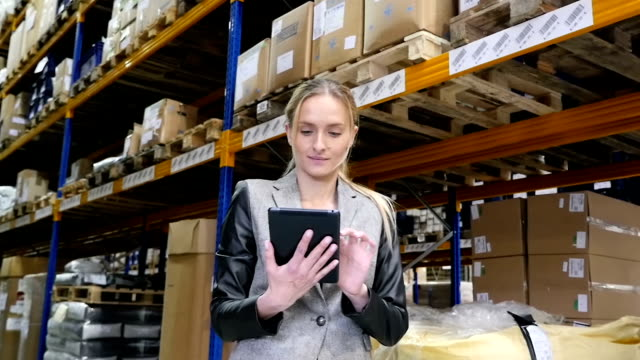 Concentrated woman working with the tablet in warehouse video