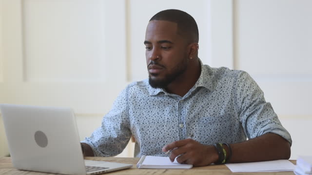 Concentrated young african ethnicity guy watching educational webinar. Concentrated young african ethnicity guy sitting at table, watching educational webinar, writing down notes, rewinding video. Focused mixed race male freelancer working remotely at home or office. adult stock videos & royalty-free footage