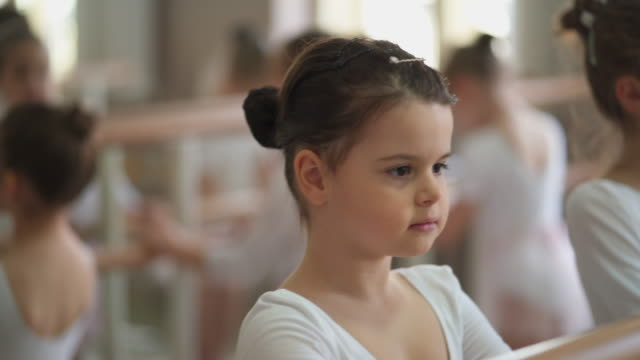 Concentrated young ballerinas on a barre class Group of young girls practicing ballet in ballet studio dance studio stock videos & royalty-free footage