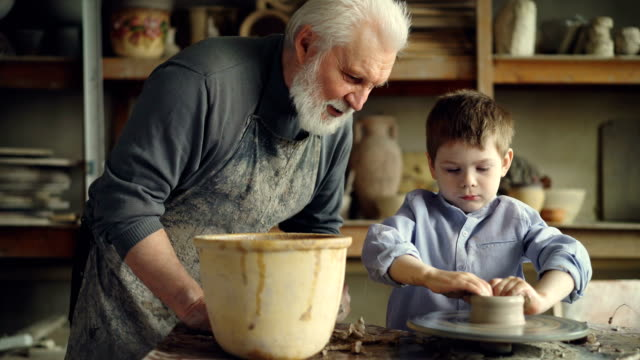 concentrated young boy is molding clay into ceramic pot on spinning throwing wheel and his experienced grandfather is talking to him. pottery and family tradition concept. - dziadek filmów i materiałów b-roll