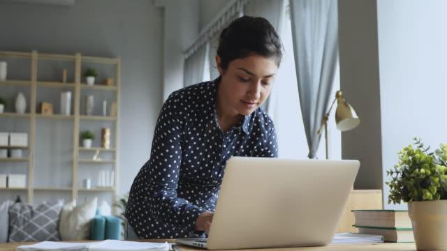 vídeos de stock, filmes e b-roll de jovem hindu concentrada trabalhando em pé no laptop na mesa. - college people laptop