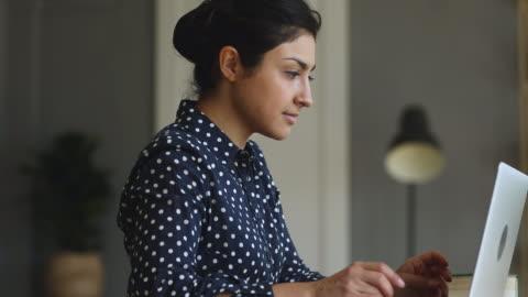 giovane imprenditrice indiana concentrata che lavora al computer a casa d'ufficio. - guardare in una direzione video stock e b–roll