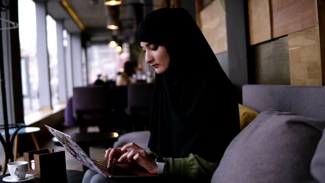Concentrated young muslim woman working on modern laptop in cafe. Attractive woman in hijab holding the laptop on her knees and typing. Side view. Slow motion