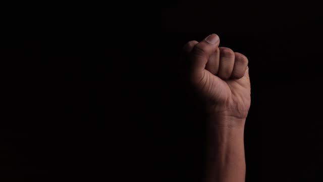 concept against racism or racial discrimination by showing with hand gestures fist or solidarity black background - pugno video stock e b–roll