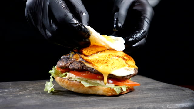 SLOW MOTION FOOD concept. Chef making burger. Close-up. Burger restaurant menu cooking process. Chef prepares fast food at restaurant putting fried egg on grilled meat. Full hd SLOW MOTION FOOD concept. Chef making burger. Close-up. Burger restaurant menu cooking process. Chef prepares fast food at restaurant putting fried egg on grilled meat. bun bread stock videos & royalty-free footage