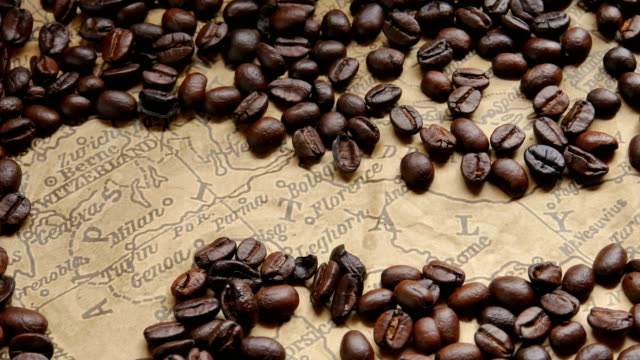 concept Coffee beans around the map of Italy.