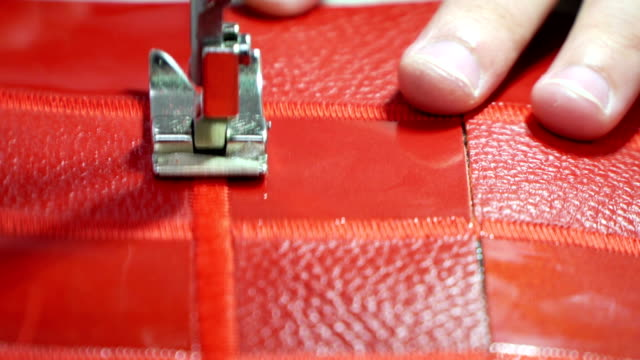 Concept factory production genuine leather goods. Stitching red leather on a sewing machine close up video