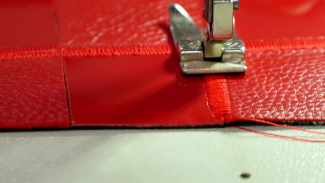 concept factory production genuine leather goods. stitching red leather on a sewing machine close up - личный аксессуар стоковые видео и кадры b-roll