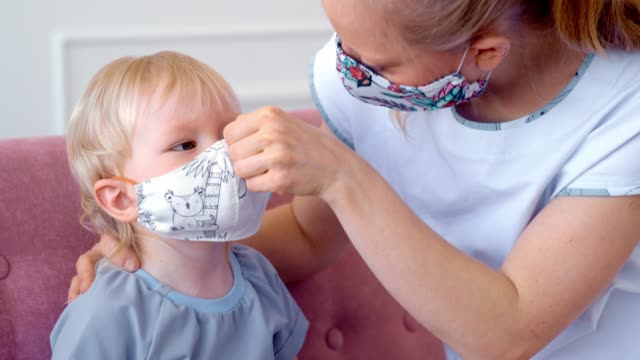 Concept, family during quarantine self-isolation. Mom puts her son in a mask for protection. video