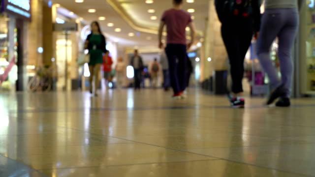 vídeos de stock, filmes e b-roll de família de conceito compras no shopping. jovens bonitas meninos e meninas com as pernas bem torneadas, andando na galeria comercial entre a multidão em borrão - shopping center