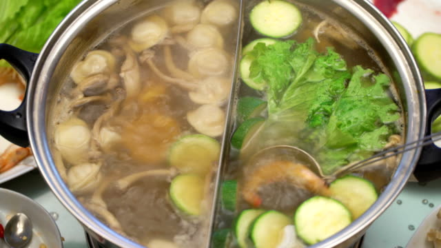 Concept Hotpot Asian cuisine. Boiling broth on the table. Cooking shrimp in skimmer spoon closeup video