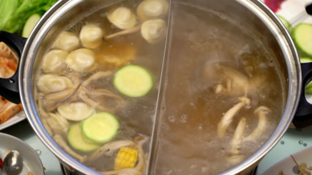 Concept Hotpot Asian cuisine. Boiling broth on the table. Corn put into the broth for cooking video