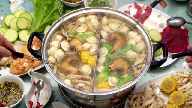 Concept Hotpot Asian cuisine. Cooking shrimp in skimmer spoon. Shrimp in hot soy sauce video
