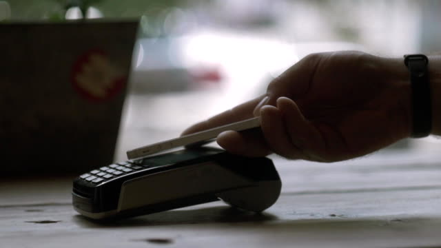 Concept NFC contactless payment. Making payment with credit card and pos terminal, printed check.