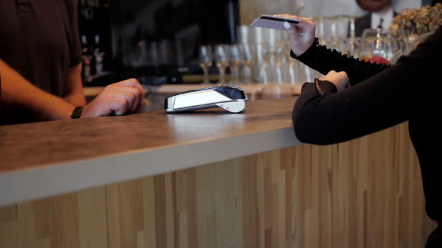 vídeos de stock e filmes b-roll de concept nfc contactless payment. making payment with credit card and pos terminal, printed check. - paying with card contactless